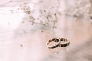 LGBT wedding rings blurred flower background